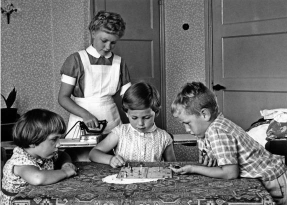 Terwijl de kinderen een potje 'Mens Erger Je Niet' spelen, staat een jonge gezinshulp te strijken, 1958. (Nationaal Archief/Spaarnestad/Pim Stuifbergen)