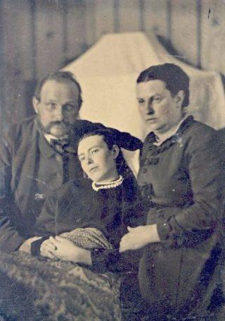 Foto uit de Victoriaanse tijd van een echtpaar dat zich laat fotograferen met hun overleden dochter