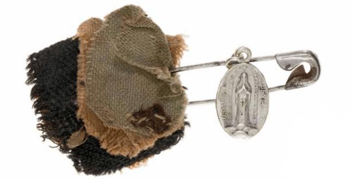 Maria verschijnt 33x in beauraing. Veiligheidsspeld aan stoffragmenten met hanger van Notre Dame de Beauraing, ca. 1930-1960 (RMCC v978)