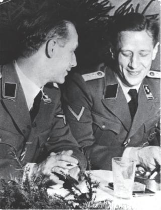 Hauptsturmführer Ferdinand aus der Fünten (rechts) had de informele leiding over de Duitse instantie die de deportaties moest uitvoeren, de Zentralstelle für jüdische Auswanderung. Op de foto zit hij naast de commandant van kamp Westerbork, A. Gemmeker, tijdens de viering van Kerstmis 1942 in het Durchgangslager. BeeldbankWO2 / NIOD
