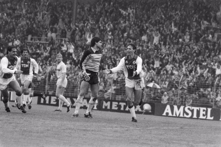 Ajax-Feyenoord 8-2. Marco van Basten juicht nadat hij de 2-0 heeft gemaakt. Feyenoord-doelman Joop Hiele baalt. (cc - Anefo - Nationaal Archief)