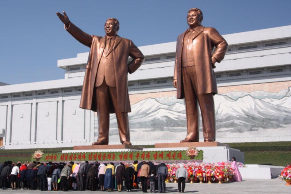 Noord-Koreanen buigen voor de standbeelden van Kim Hong-Un's vader en grootvader - cc