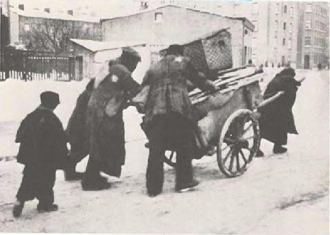 Een joodse familie op weg naar het getto is. Opvallend is dat de joodse bevolking zowel op de voorzijde als op de achterzijde een jodenster moest dragen.  (The Chronicle of the Lodz Ghetto - Yale, 1987)