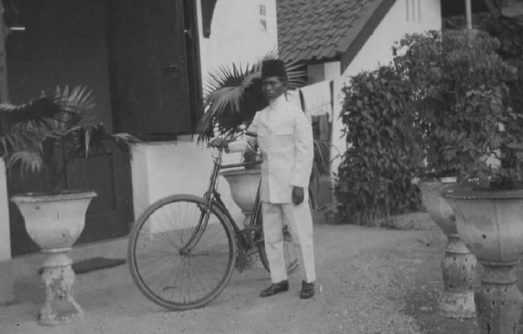 Huisjongen met een fiets te Soerabaja, circa 1925 (KITLV)