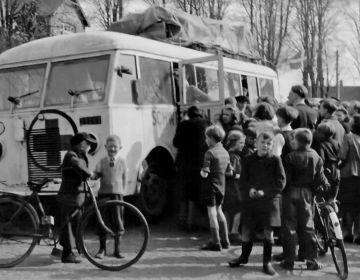 Zweedse witte bus met Deense Joden, opgehaald in Theresienstadt (Tsjechië) maakt een tussenstop in het Deense Haderslev op weg naar Zweden ( foto collectie Museum Kamp Frøslev)