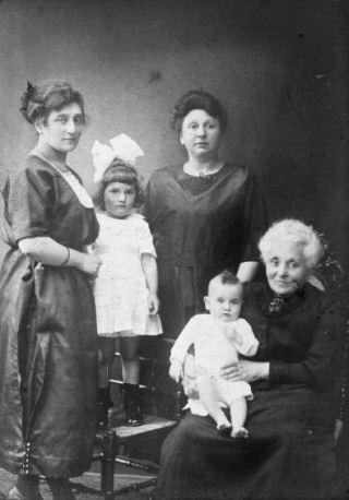 De familie van Mimi in vroeger tijden. Van links naar rechts: Tilly Schenk, de moeder van Mimi die hier zelf op de stoel staat, oma Francien Schenk-van Brink en overgrootmoeder Geertrui van Brink-Schenk met op haar schoot Alex, de oudste broer van Mimi. Foto: Mevrouw J.J. Snijders-Polak