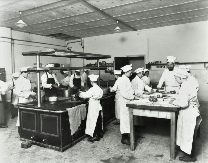 Een jonge Iwan Kriens houdt toezicht in de keuken tijdens een kookles (1914). Foto Collectie London Metropolitan Archives.