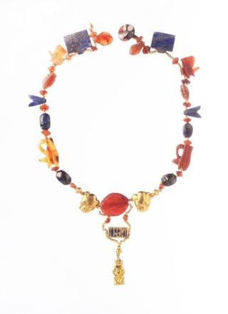 Deze halsketting uit het Nieuwe Rijk (1539-1077 v. Chr.) is geregen uit kralen en verschillende beschermende en kwaad afwerende amuletten: Horusogen, scarabeeën, vissen, vliegen, een ornament met Hathorkoe, panterkopjes en een hanger in de vorm van de dwerggod Bes. (Foto RMO Leiden)