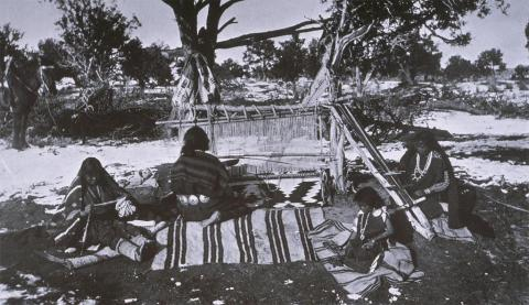 Group of weavers: woman on the left is spinning yarn, small girl is carding