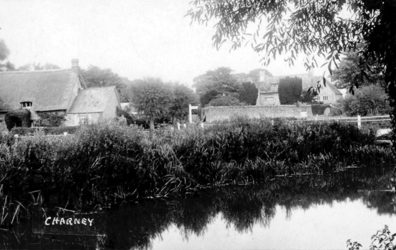 Postcard view of Charney and river and one of the thatched cottages at the entrance to the village to the left of the Church. No date.