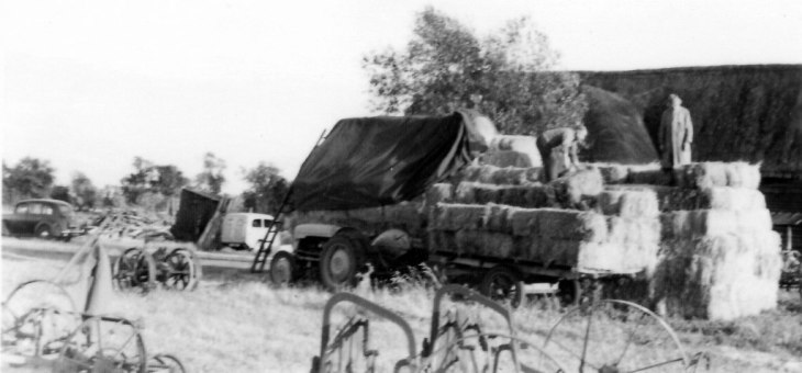 Stacking bales outside Minmere Barn c1960