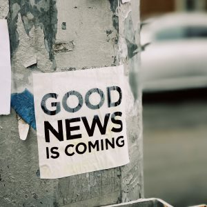 """Sign on post, says """"good news is coming"""""""