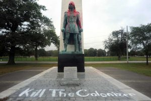 statue covered in red paint and graffiti that reads: Kill The Colonizer