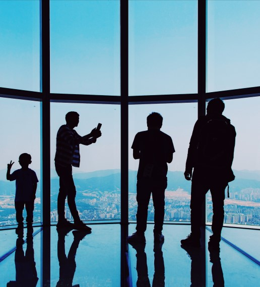 Silhouette of four people standing in a highrise building, one person appears to be taking a selfie with their child. You can see a city below.