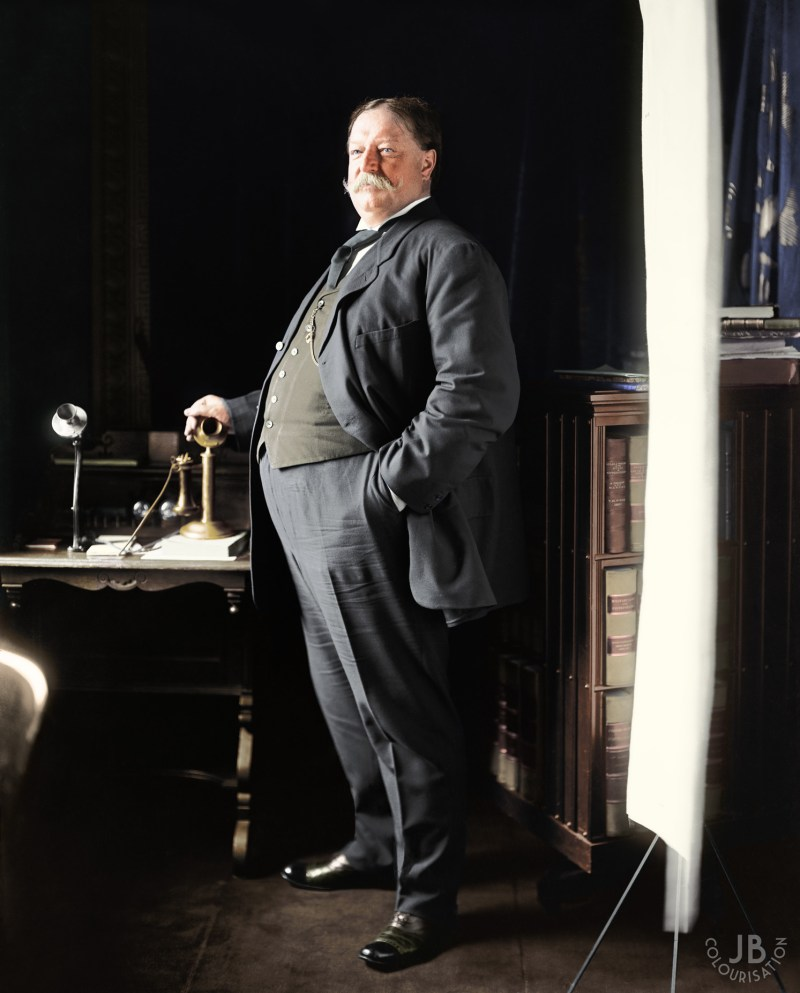 William Howard Taft standing in an office. The photo is colorized.