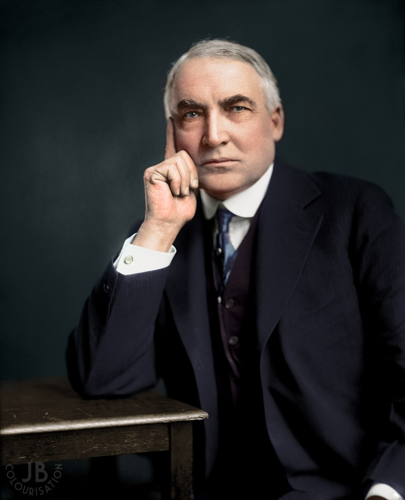 Color photograph of Warren G. Harding leaning on a table with his hand on his face. This photo has been colorized.
