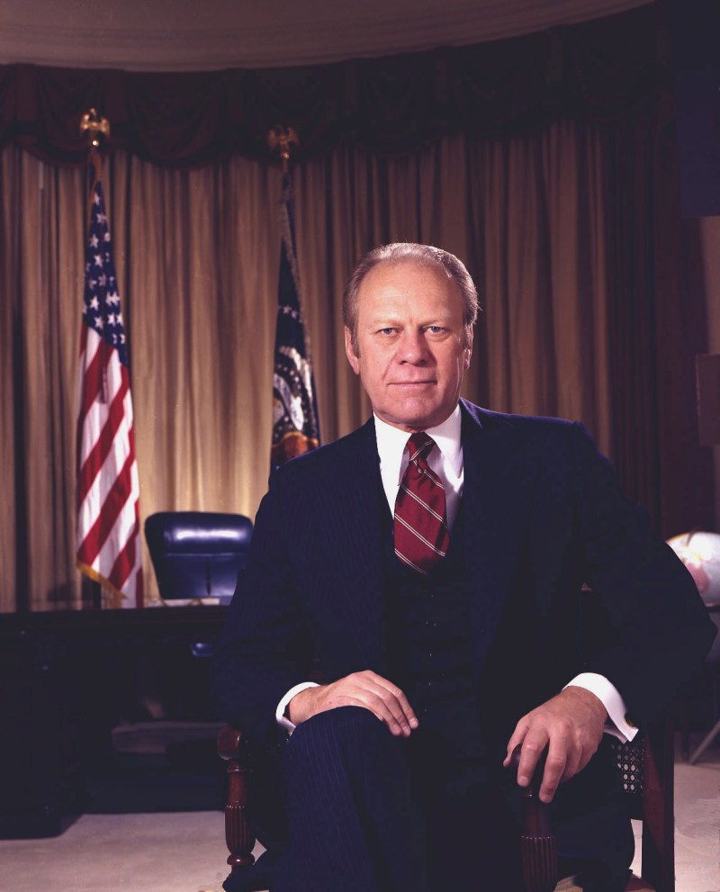 President Gerald Ford sitting on a chair in front of his office and the American flag.