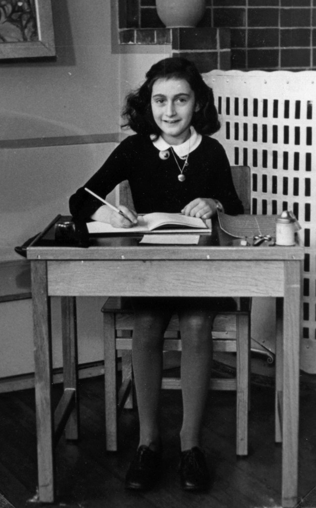 Anne Frank writing in a book while sitting on a chair behind a desk and looking at the camera.