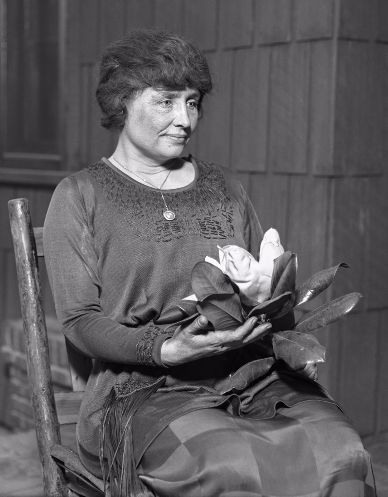 Helen Keller holding a magnolia flower.