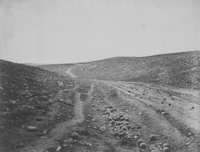 Famous photograph the valley of the shadow of death. It shows a dirt road in a valley in the Crimea, with cannonballs scattered across the road.