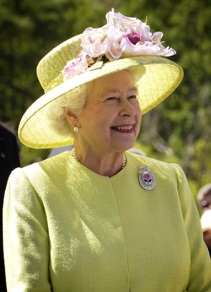 Queen Elizabeth II of the United Kingdom in a yellow hat and yellow clothing smiling in 2007. She is related to the Tudor monarchy.