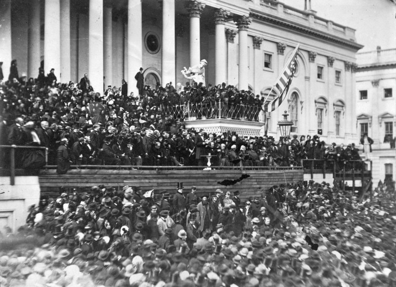 A huge crowd surrounds Abraham Lincoln outside of the US Capitol building. March 1864