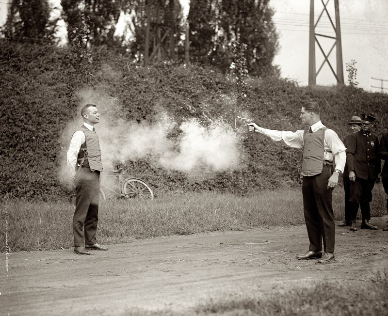 A man aiming a gun at another person wearing a bulletproof vest. Smoke from the barrel surrounds them and onlookers watch on. September 1923.