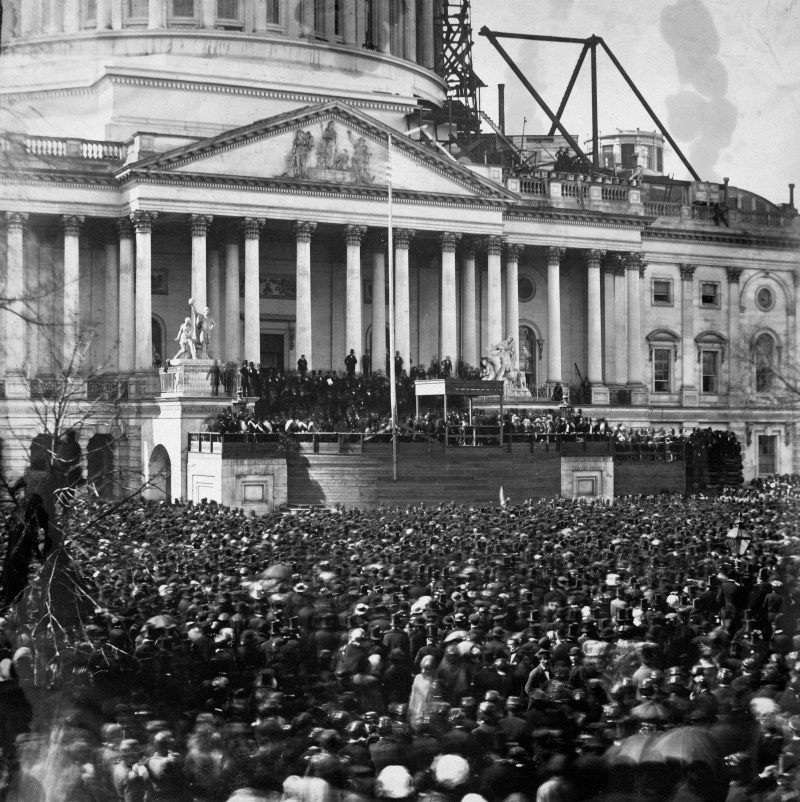 A photograph of the first inauguration of Abraham Lincoln. Thousands of people are crowded around the capitol building in Washington, D.C. that is under construction in 1861.