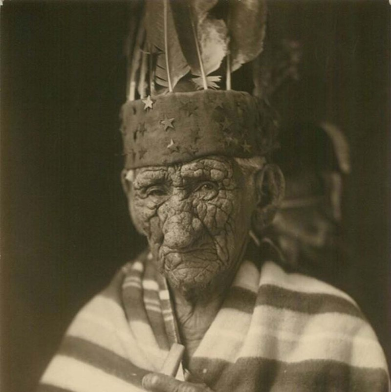 Chief John Smith with a cover wrapped around him wearing a head band covered in stars with feather coming from the top.