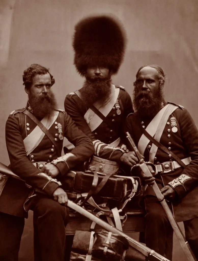 Three British army soldier in full military uniform in a photo studio along with their weapons and medals. 1856
