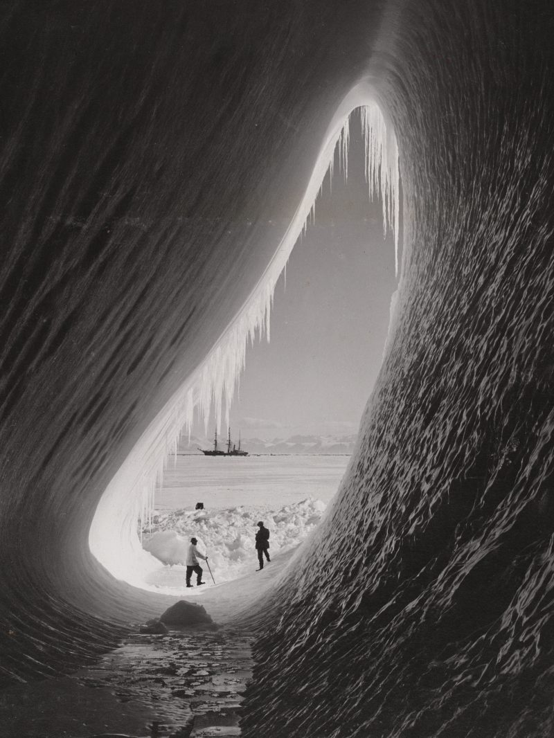 Photograph of two men standing in icy grotto within an iceberg during the Terra Nova expedition with the ship in the background in 1911.