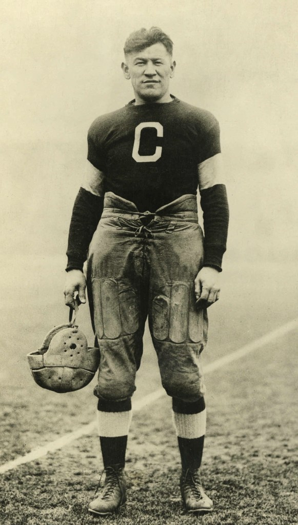 "Legendary athlete, Jim Thorpe holding a helmet and wearing his Canton Bulldogs uniform in circa 1917. He is looking directly at the camera and has a big ""C"" on his chest."
