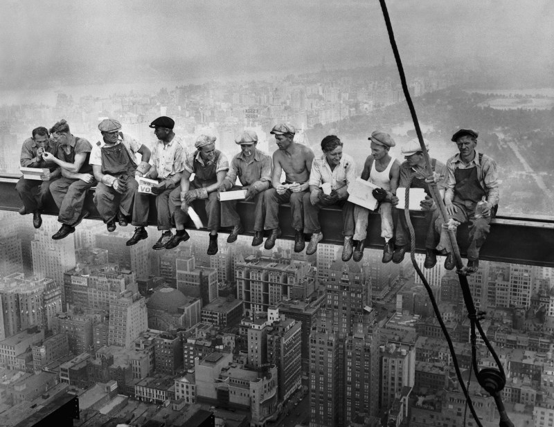 The famous historical photograph, Lunch atop a skyscraper showing workers sitting on a steel beam above the skyline of Manhattan in 1932.