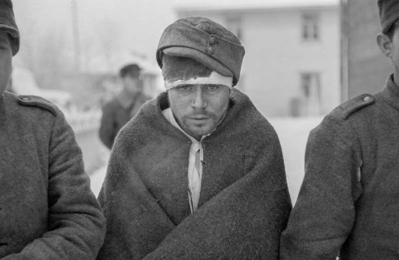 An injured Prisoner of War from the Soviet Union with a bandage around his bloody head, with clothing wrapped around his body. He looks cold as he is near the Arctic Circle where temperatures can get to -43 degrees Celsius