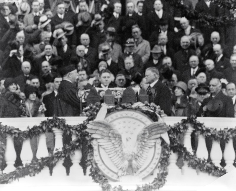 Herbert Hoover at his inauguration doing the oath of office which is being administered by Chief Justice Taft, who was also a US President. They are surrounded by a crowd. 1929.