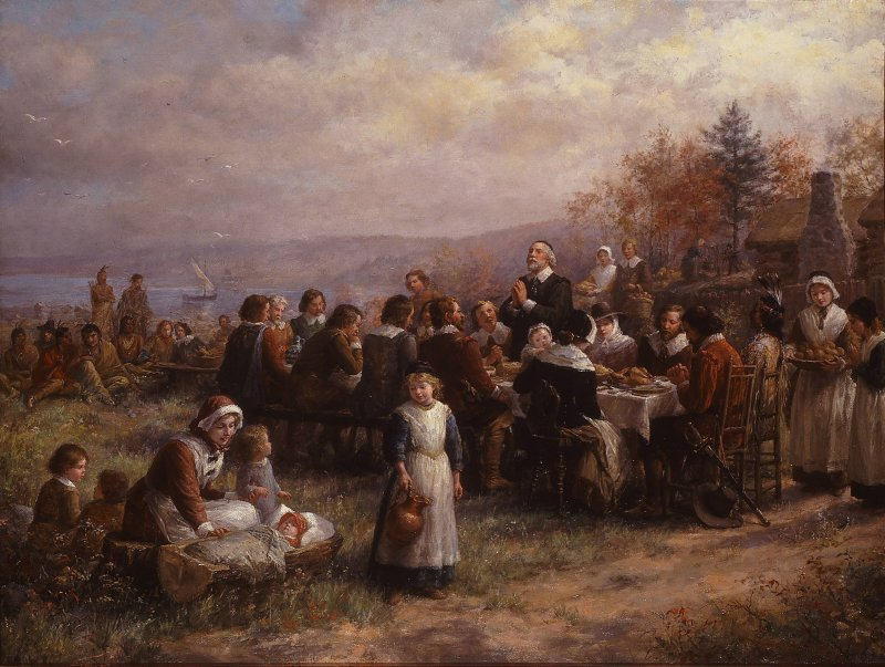 A group of pilgrims and native americans taking part in the first Thanksgiving at Plymouth