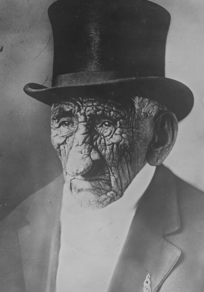 White Wolf Chief John Smith pictured wearing a top hat and suit. You can clearly see his heavily wrinkled face in this image.