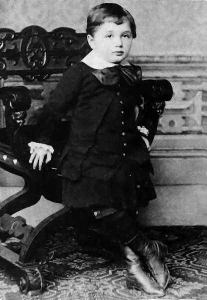 Albert Einstein photographed during his child hood wearing formal clothing and leaning on a chair at the age of 3.