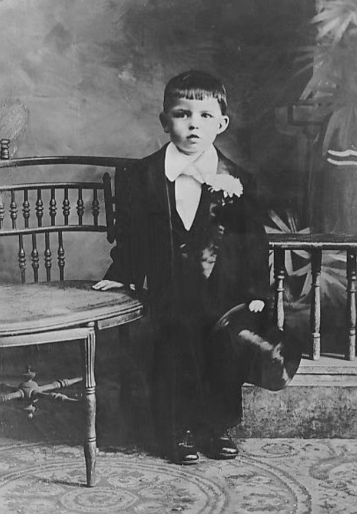 Frank sinatra as a child around the age of 3 in a suit and top hat with his hand on a chair