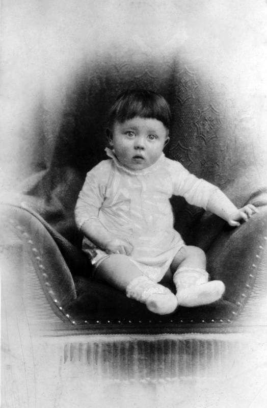 Baby Adolf Hitler sitting on a chair posing for a professional photograph in c. 1890