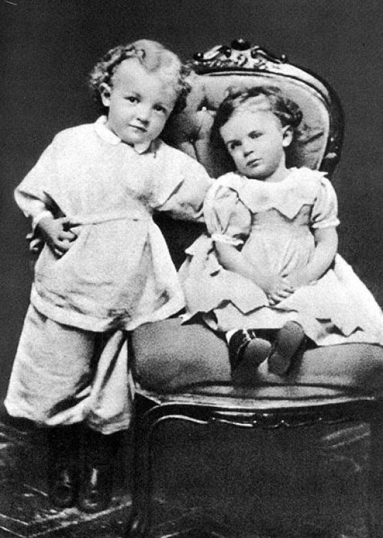 Vladimir Lenin as a child at the age of 3 standing next to a chair with another person sat in the chair.