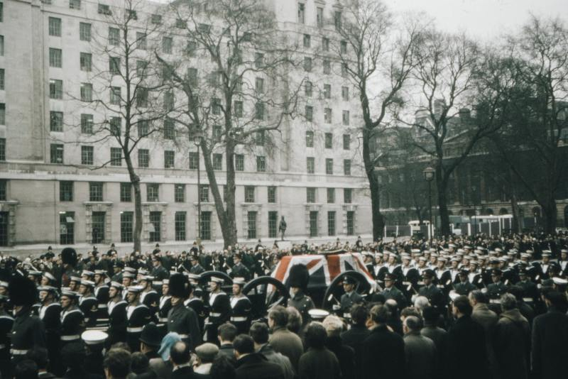a crowd watching the coffin, that is draped with a union flag, of Winston Churchill pass by in London.