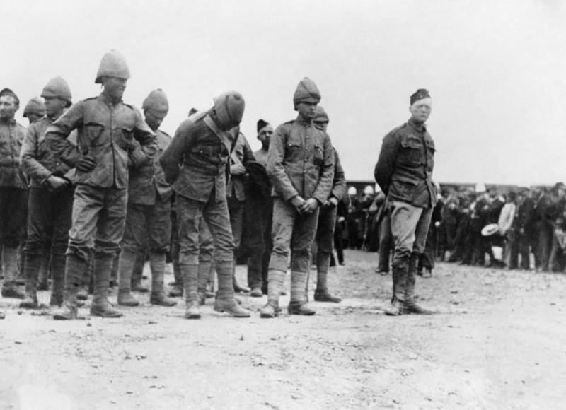 Winston Churchill wearing a uniform standing on the right of a group of prisoners during the Second Boer War, 1899.