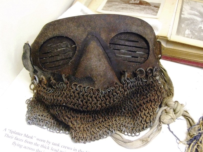 Chainmail splatter mask on display at a museum.