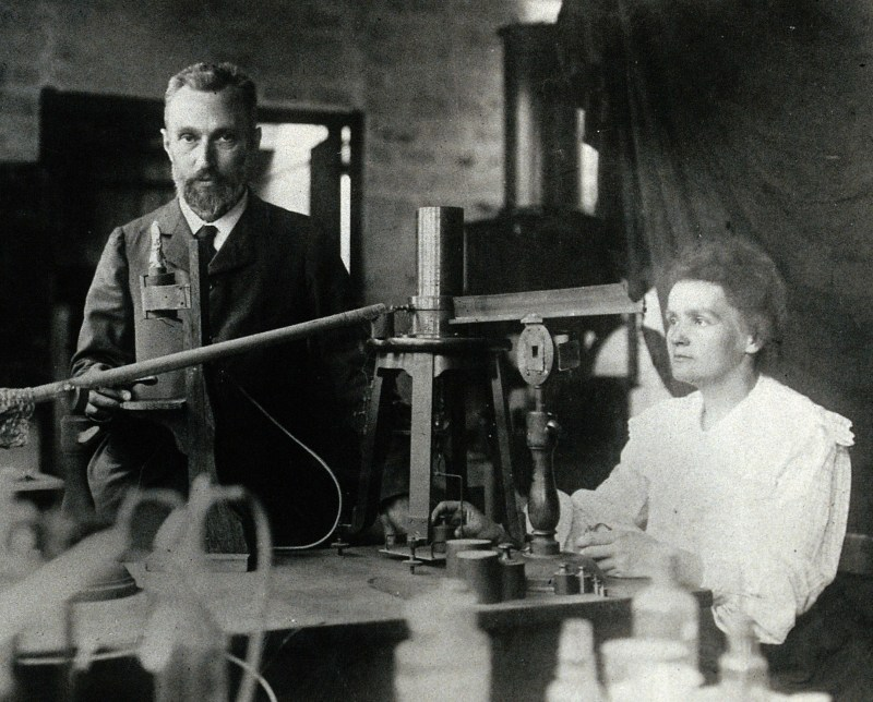 Pierre and Marie Curie in the laboratory, demonstrating the experimental apparatus used to detect the ionisation of air, and hence the radioactivity, of samples of purified ore which enabled their discovery of radium.