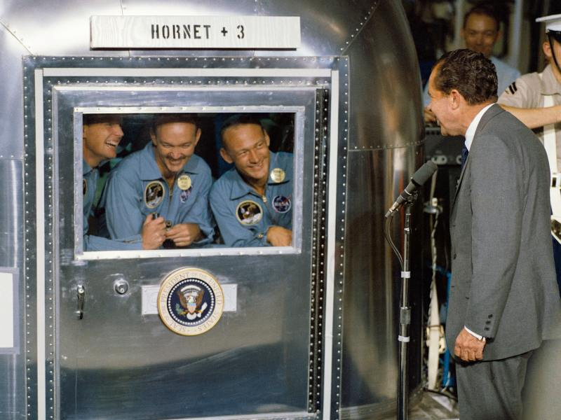 Neil Armstrong, Michael Collins, and Buzz Aldrin inside the Hornet 3 quarantine speaking to Richard Nixon