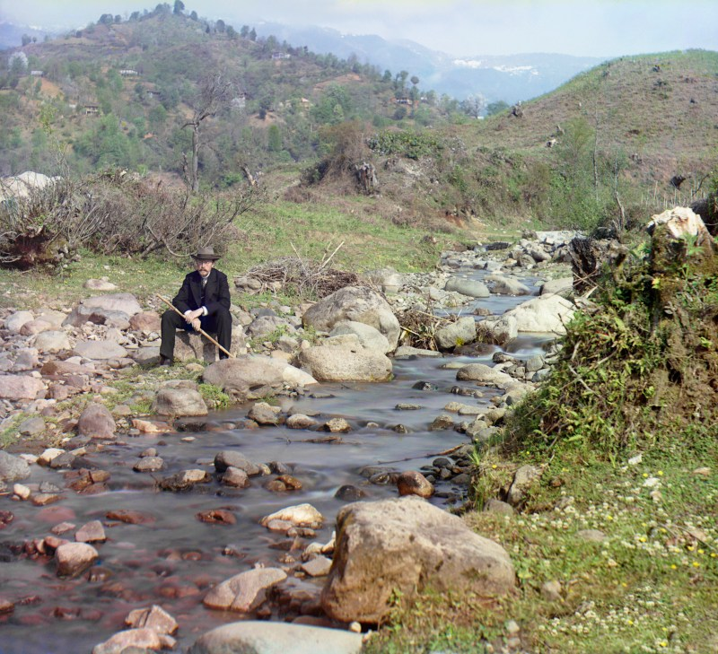 Sergey Prokudin-Gorsky holding a cane and sitting on a rock by a river with mountains in the background in color