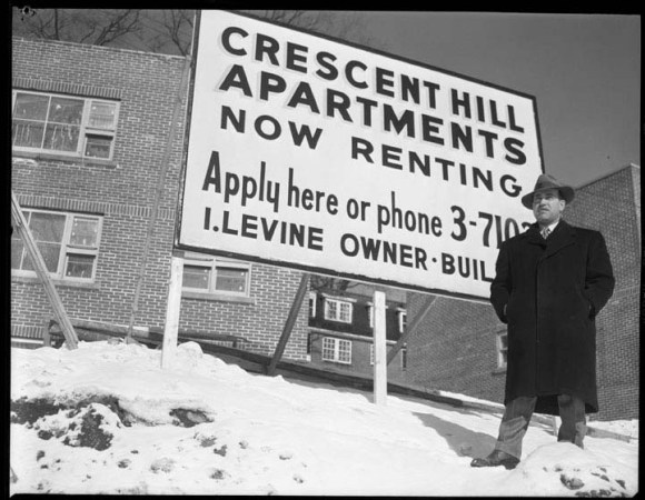 Isaac Levine in front of his Crescent Hill Apartments, a seven building cluster along Chapleau street in New Edinburgh. February 12, 1954. He completed the project later that spring. Source: City of Ottawa Archives, Itemo CA003188.