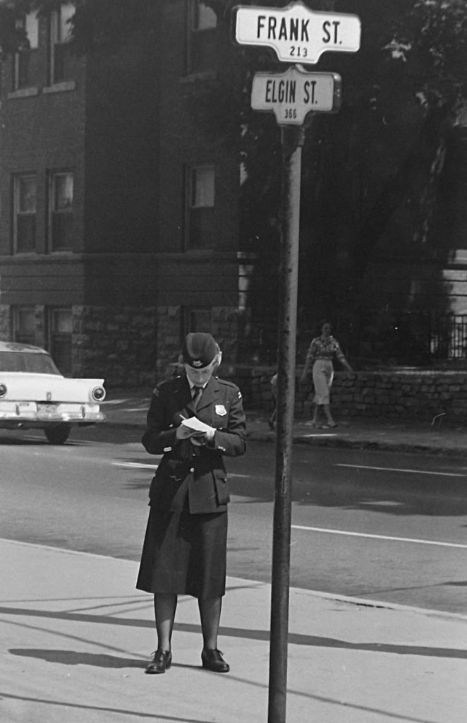 An officer writes a ticket at the corner of Elgin and Frank streets, 1960. Image: Ted Grant / LAC Accession 1981-181 NPC Series 60-695A.