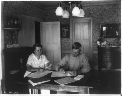 Farm couple working on their bookkeeping at dining room table, ca. 1930